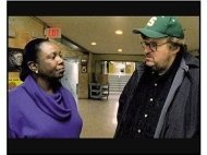 Bowling for Columbine movie still: Michael Moore talks with Principal Hughes at Buell Elementary School in michigan about the shooting of a six--year--old girl -- by another six--year--old in Bowling